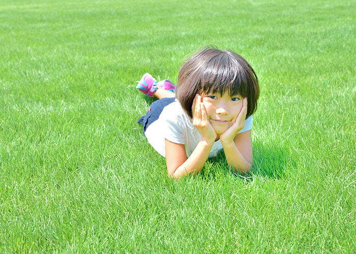 芝生に寝転び肘をついている女の子