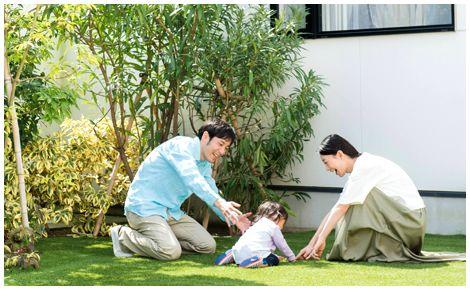 中庭の芝生でくつろぐ親子
